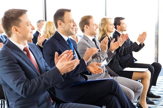 Publikum von glücklichen geschäftsleuten, die im schulungsraum, im konferenzsaal sitzen und dem sprecher applaudieren