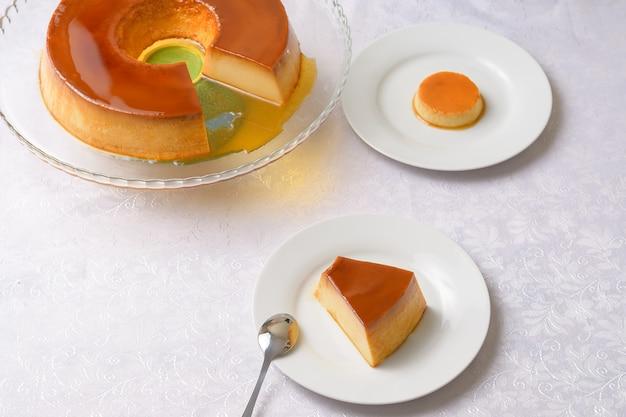 Pudding auf einem transparenten teller und eine scheibe pudding auf einem weissen teller