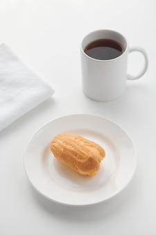 Pudding eclair kuchen liegt auf einem weißen teller mit einem glas auf dem hintergrund.