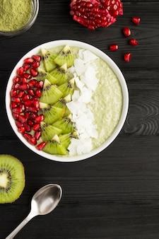 Pudding mit chia, matcha-tee, kiwi, granatapfelkernen und kokosflocken in der weißen schüssel