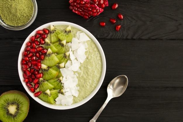Pudding mit chia, matcha-tee und früchten in der weißen schüssel