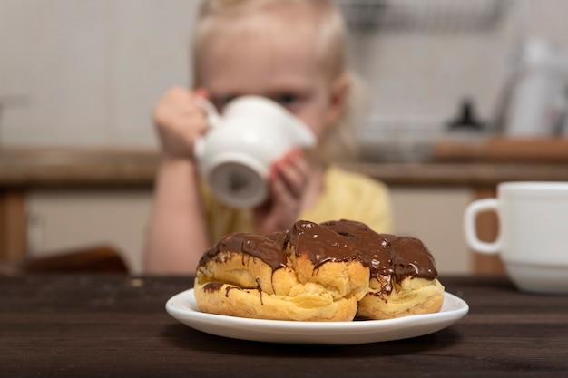 Puddingkuchen auf dem tisch. kleines mädchen auf der oberfläche trinkt eine milch. frühstück mit kind.