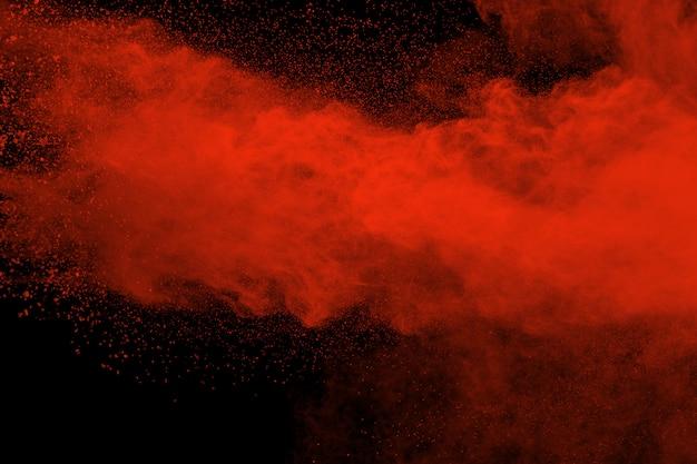 Puderexplosion der roten farbe auf schwarzem hintergrund