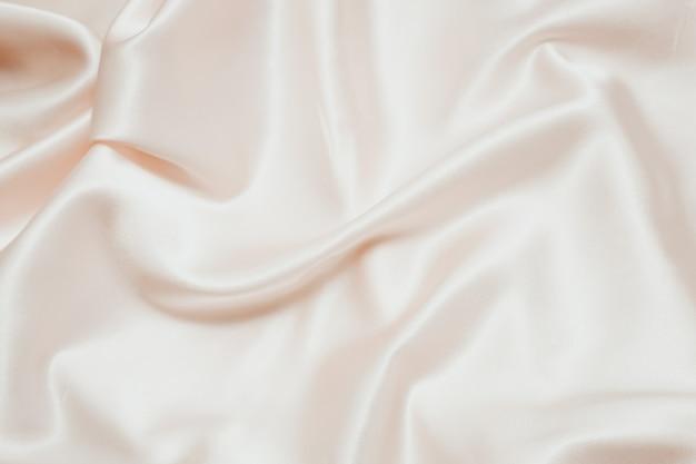 Puderrosa textur aus seide, satin. glänzender stoffhintergrund.