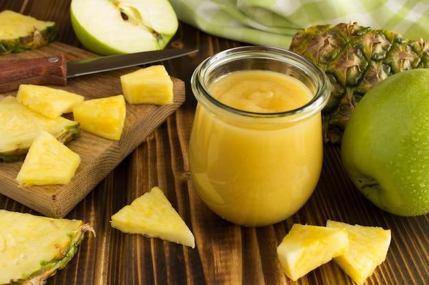 Püree mit ananas und apfel auf dem holzuntergrund