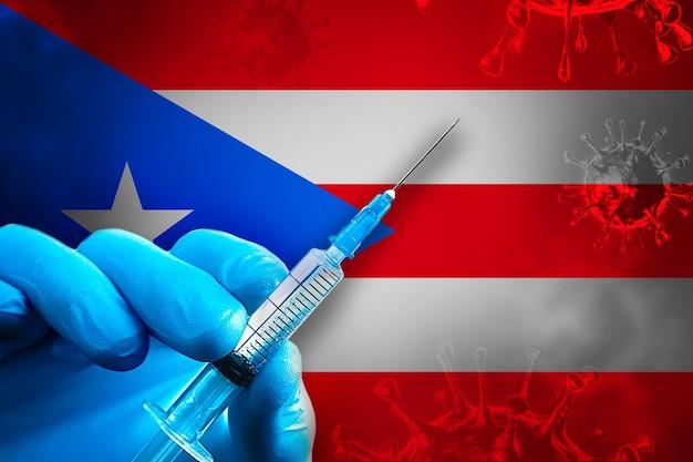 Puerto rico covid19-impfkampagne hand in einem blauen gummihandschuh hält spritze vor flagge