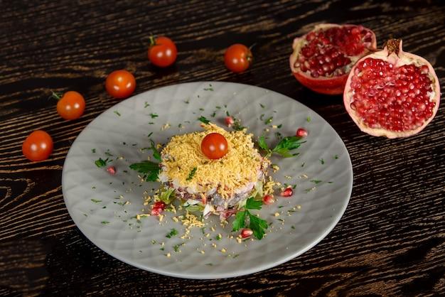 Puff salat mit fleisch, gemüse, käse, eiern, garniert mit kräutern und granatapfel und kirschtomaten auf einem grauen teller. vor dem hintergrund von granatapfel- und kirschtomatenhälften.