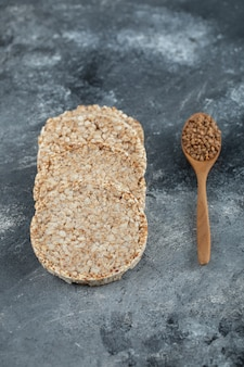 Puffed crispbread und holzlöffel rohen buchweizens auf marmoroberfläche