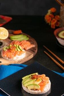 Puffreisaufstrich mit rohem lachs und avocado auf einem dunklen tisch