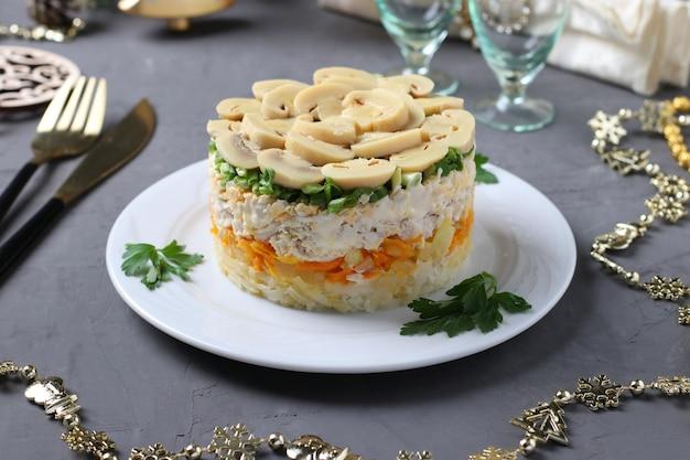 Puffsalat mit hühnchen, eingelegten pilzen, kartoffeln und karotten auf tellern. neujahrskomposition.