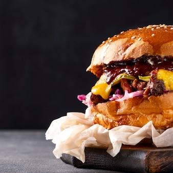 Pulled pork burger mit zwiebeln, kohl und käse auf holzbrett