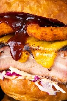 Pulled pork burger mit zwiebelringen, käse, kohl und salat. nahaufnahme, makroansicht
