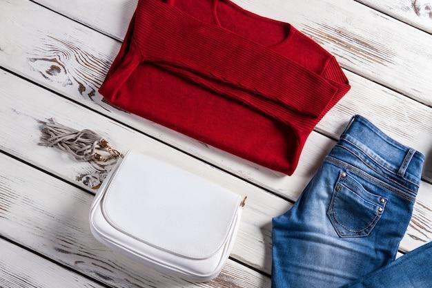 Pullover mit handtasche und jeans. damenbekleidung auf regal. kleiderverkauf mit rabatten. damenbekleidung im lokalen geschäft.