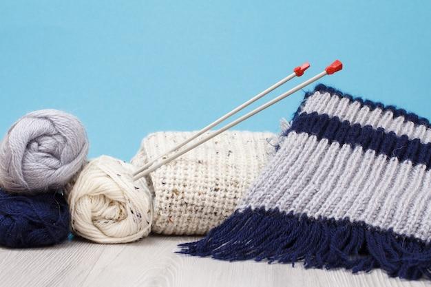 Pullover, schal und garnstränge mit metallstricknadeln auf grauen brettern und blauem hintergrund. strickkonzept.