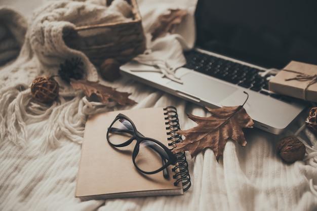 Pullover und eine tasse tee mit notebook, laptop und strickkleidung