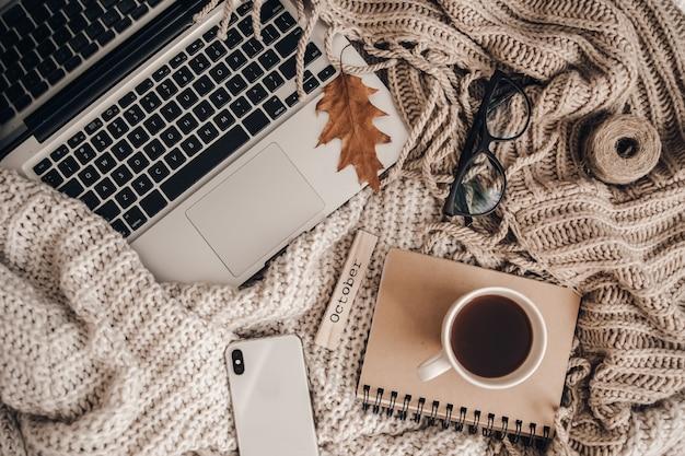 Pullover und eine tasse tee mit notebook, laptop und telefon