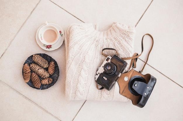 Pullover und kamera in der nähe von kaffee und tannenzapfen gelegt
