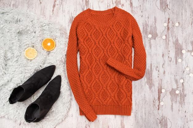 Pullover und schwarze schuhe auf einem hölzernen hintergrund