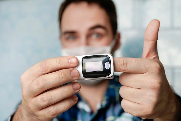 Pulsoximeter am finger ist eine gute möglichkeit, den blutsauerstoffgehalt im falle einer virusinfektion der lunge zu testen. hoher sättigungsindex, gesunder junger mann. es zeigt, dass alles in ordnung ist.