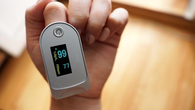 Pulsoximeter am finger zeigt sauerstoffsättigung und herzfrequenz an