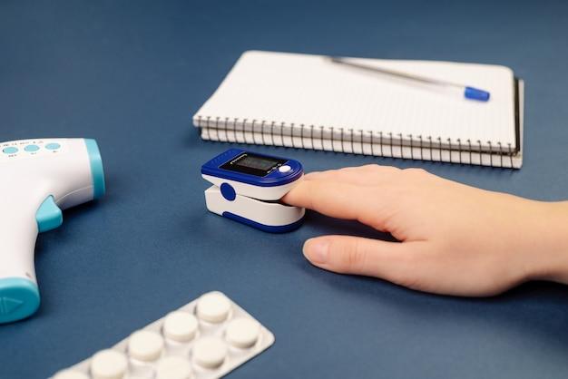 Pulsoximeter am finger zur messung der pulsfrequenz und des blutsauerstoffsättigungsniveaus zur überprüfung der lunge auf virusinfektion, lungenentzündung oder coronavirus mit pillen, notizbuch und thermometer auf blauem hintergrund.