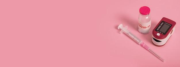 Pulsoximeter, coronavirus-impfstoff und spritze auf rosafarbenem hintergrund. diagnose von covid 19. pandemie 2021.banner