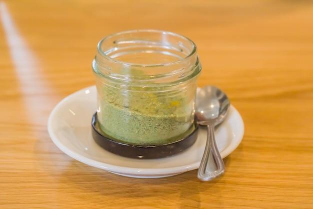 Pulver aus grünem tee wird in eine glasflasche auf dem tisch gegeben.