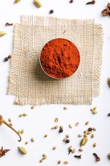 Pulver der roten paprikas des indischen gewürzs in der schüssel auf weißer tabelle