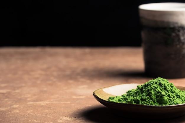 Pulver des grünen tees mit keramischer schale auf dem tisch, schwarzer hintergrund. freier platz für text