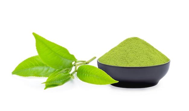 Pulver von grünem tee und grünem teeblatt auf weißem hintergrund