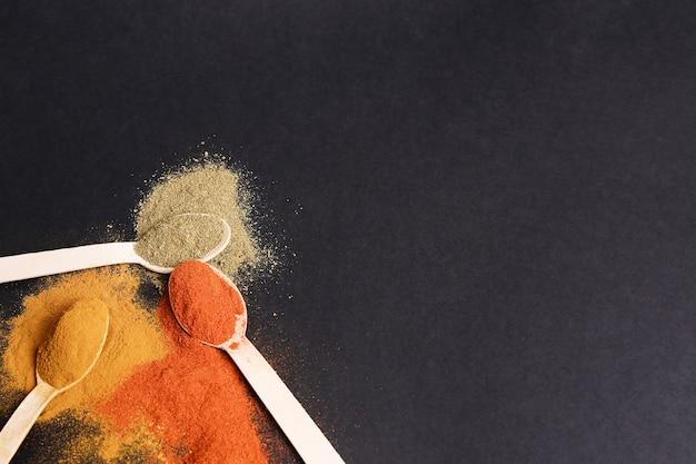 Pulvergewürz auf schwarzem tisch, draufsicht