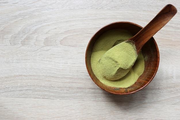 Pulverisieren sie matcha grünen tee in einer schüssel auf holz