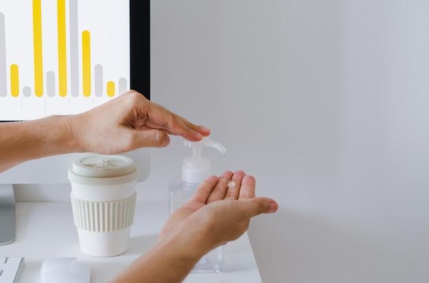 Pumpen sie alkoholgel von hand aus der flasche, um das virus im büro zu reinigen und zu schützen.