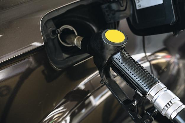 Pumpen von benzinkraftstoff in braunem auto an der tankstelle
