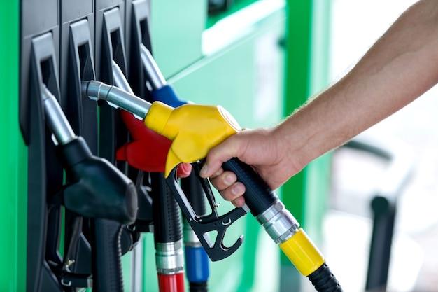 Pumpen von gas an der zapfsäule. nahaufnahme des mannes, der benzinkraftstoff im auto an der tankstelle pumpt.