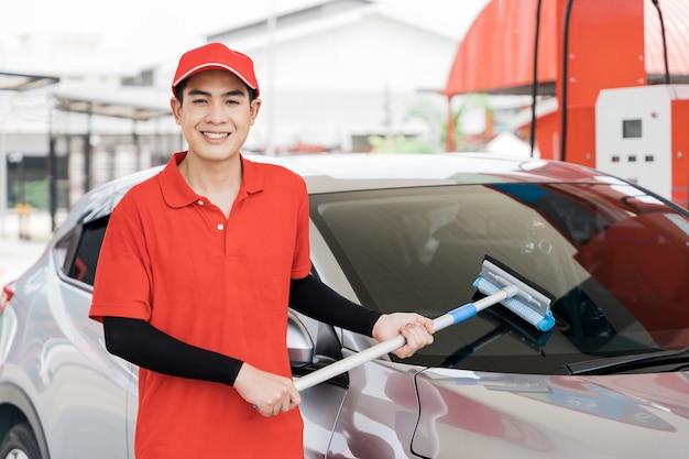 Pumpenarbeiter, der autofenster an der tankstelle wäscht