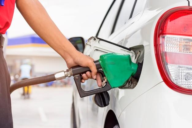 Pumpgas an der zapfsäule. nahaufnahme des pumpenden benzinbrennstoffs des mannes im auto an der tankstelle