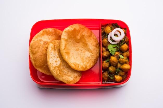 Punjabi chole oder choley masala mit puri oder poori in lunchbox oder tiffin, selektiver fokus