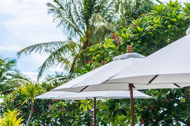 Punkt des selektiven fokus auf regenschirm mit kokosnusspalme auf dem hintergrund für feiertagsferien