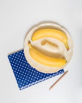 Punktiertes notizbuch mit bananen auf platte