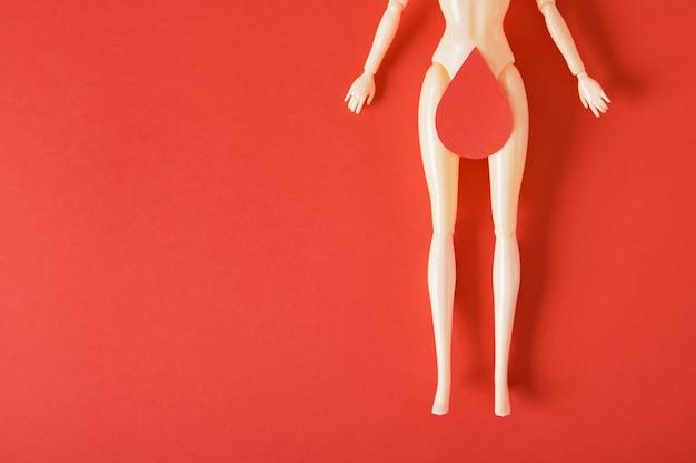 Puppe mit einem papiertropfen blut an den oberschenkeln, feminismuskunst, frauengesundheits- und gnekologiekonzept, menstruationsroter hintergrundkopierraum