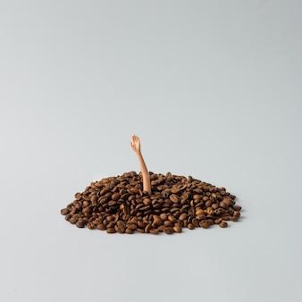 Puppenhand, die von einem stapel kaffeebohnen auftaucht