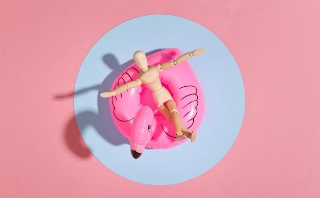 Puppenpuppe mit aufblasbarem flamingo auf rosa blau hell. konzept für strandurlaub. sommerruhe. minimalismus