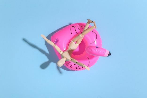 Puppenschaufensterpuppe mit aufblasbarem flamingo auf blauem hellem. konzept für strandurlaub. sommerruhe. minimalismus