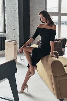 Pure schönheit. die volle länge der attraktiven jungen frau in einem eleganten schwarzen kleid mit einem tiefen schlitz posiert, während sie in der nähe des sofas steht
