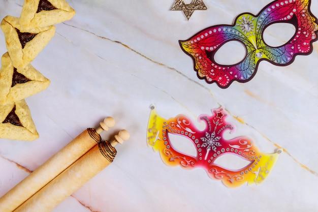 Purim abstrakter hintergrund mit masken, keksen und schriftrolle.