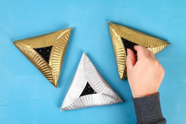 Purim. diy kekse hamantaschen von pappplatten mit süßen überraschungen im inneren