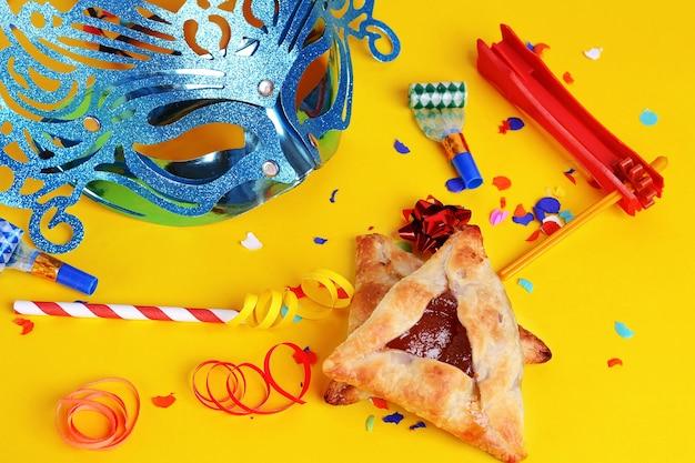 Purim-hintergrund mit karnevalsmaske, parteikostüm und hamantaschen plätzchen.