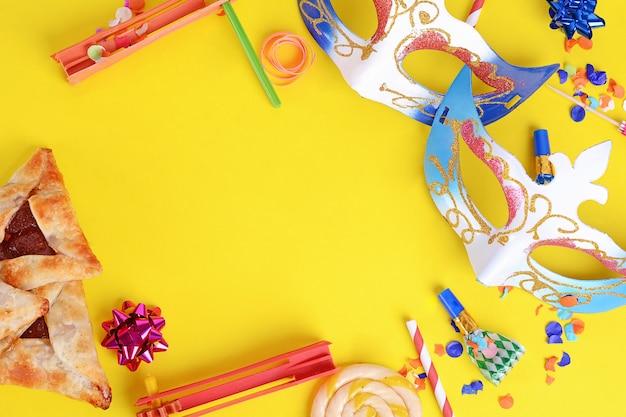 Purim-hintergrund mit karnevalsmaske, partykostüm und hamantaschen-keksen.