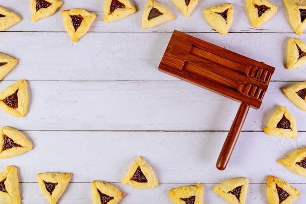 Purim hintergrund mit noise maker und hamantaschen cookies.